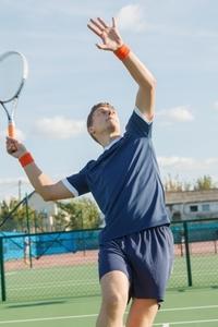 テニスのサーブをする男性