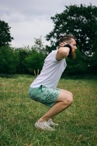 スクワットを行う男性。膝が出ているダメな例