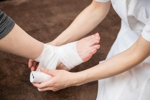 弾性包帯を巻いてもらう女性の足