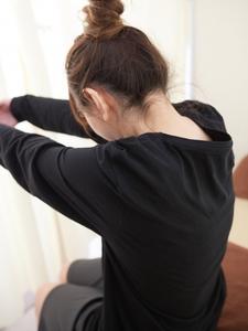 座りながら背中のストレッチを行う女性