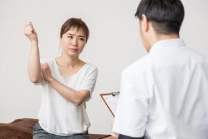 腕の痛みを訴える女性