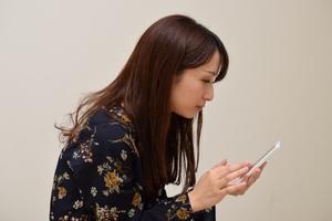 悪い姿勢でスマートフォンを操作する女性