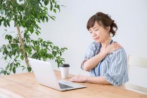 デスクワークで肩が疲れた女性の写真