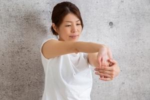 前腕屈筋群をストレッチする女性