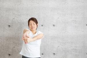 前腕屈筋群のストレッチをする女性(遠目)