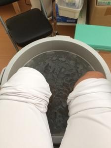バケツの氷水で足を冷やす男性