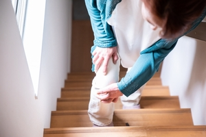 階段を登る時に膝を押さえる中高年の女性