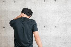 首が痛くて、手で押さえている男性の写真