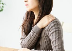 首・肩を押さえる女性の写真