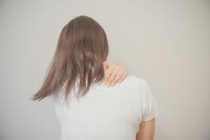 肩を押さえる女性の写真