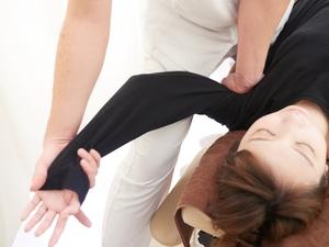 腋窩後面の筋肉のストレッチを受ける女性