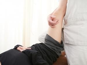 仰向けに寝た状態で太ももの裏面をストレッチされる女性