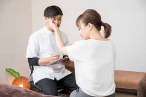 肩関節に対して問診を受ける女性