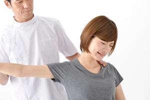 腕を横に上げられて痛がる女性