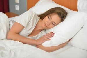 横向きで寝る女性の写真