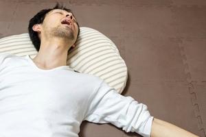 仰向けで寝る男性