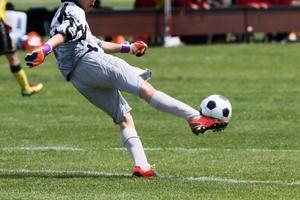 サッカーでボールを蹴る少年