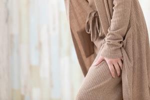 歩行中に太ももの前・股関節前部を押さえる女性