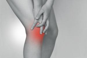 膝の前側を押さえる女性