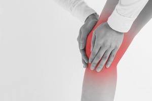 膝全体を押さえる女性の写真