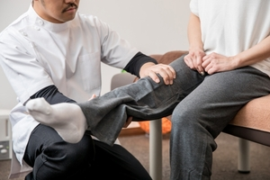 膝を他動的に伸展される女性
