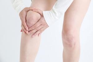 膝のお皿の周りを押さえる女性