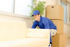 ソファを持ち上げる男性作業員