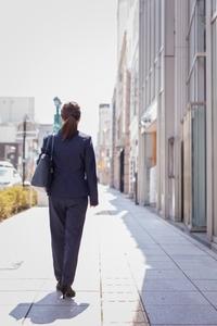 歩いているスーツを着た女性