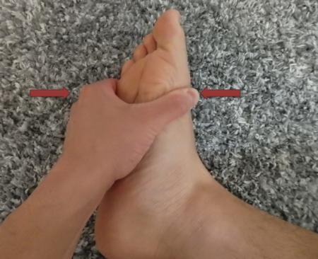 足の母指球と小指球をつまむ