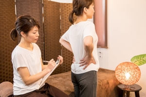 腰・骨盤を押さえる女性