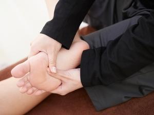 足裏を押さえる女性